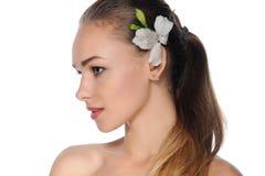 Mujer con la piel perfecta con una flor blanca en su pelo Fotos de archivo libres de regalías