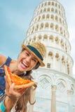 Mujer con la pizza delante de la torre inclinada de Pisa Imágenes de archivo libres de regalías