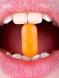 Mujer con la píldora en dientes Imagen de archivo