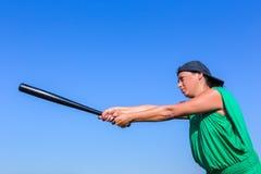 Mujer con la postura del cuerpo del bate de béisbol a pegar Foto de archivo