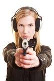 Mujer con la protección auditiva del arma y Imagen de archivo