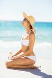 Mujer con la protección solar en la playa Foto de archivo