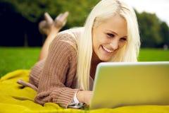 Mujer con la risa de la computadora portátil Foto de archivo libre de regalías