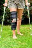 Mujer con la rodilla en apoyo después de lesión Imagen de archivo