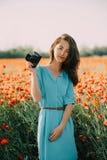 Mujer con la situación de la cámara de la foto en prado fotos de archivo libres de regalías