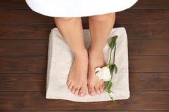 Mujer con la situación lisa en piso de madera, visión superior de los pies, de la flor y de la toalla Spa imagenes de archivo