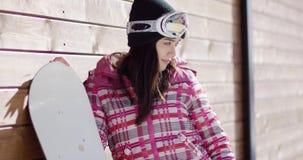 Mujer con la snowboard cerca de la pared de madera almacen de metraje de vídeo