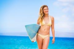 Mujer con la tabla hawaiana en la playa Imagenes de archivo