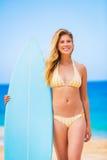 Mujer con la tabla hawaiana en la playa Foto de archivo libre de regalías