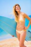 Mujer con la tabla hawaiana en la playa Fotos de archivo
