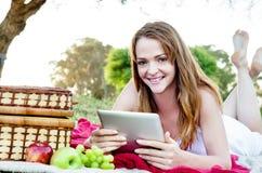 Mujer con la tableta del ipad en parque Fotografía de archivo libre de regalías