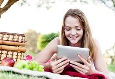 Mujer con la tableta del ipad en parque Fotos de archivo libres de regalías