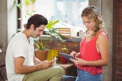 Mujer con la tableta digital mientras que hombre que usa smartphone en oficina Imágenes de archivo libres de regalías