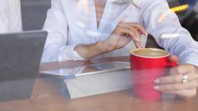 Mujer con la tableta digital que se sienta en café con café almacen de metraje de vídeo