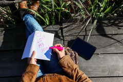 Mujer con la tableta digital y las notas en naturaleza - ame mi trabajo foto de archivo