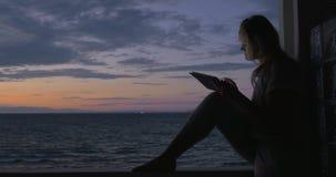 Mujer con la tableta en el balcón en la casa de la playa almacen de metraje de vídeo