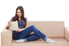 Mujer con la tableta en el sofá Imágenes de archivo libres de regalías