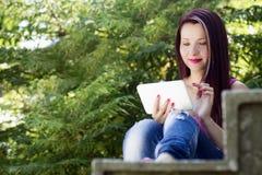 Mujer con la tableta en naturaleza Imagen de archivo