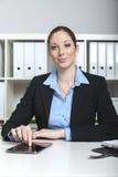 Mujer con la tableta en su lugar de trabajo Foto de archivo libre de regalías