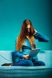 Mujer con la tableta que se sienta en color del azul del sofá Imagen de archivo libre de regalías