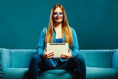 Mujer con la tableta que se sienta en color del azul del sofá Fotos de archivo