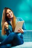 Mujer con la tableta que se sienta en color del azul del sofá Fotografía de archivo