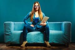 Mujer con la tableta que se sienta en color del azul del sofá Foto de archivo libre de regalías