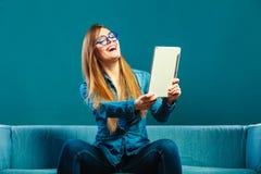 Mujer con la tableta que se sienta en color del azul del sofá Fotos de archivo libres de regalías