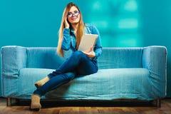 Mujer con la tableta que se sienta en color del azul del sofá Imagenes de archivo