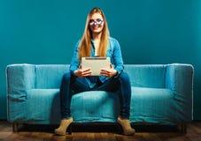 Mujer con la tableta que se sienta en color del azul del sofá Imagen de archivo