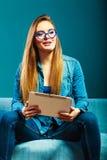 Mujer con la tableta que se sienta en color del azul del sofá Imágenes de archivo libres de regalías
