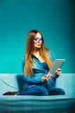 Mujer con la tableta que se sienta en color del azul del sofá Foto de archivo