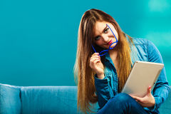 Mujer con la tableta que se sienta en color del azul del sofá Fotografía de archivo libre de regalías