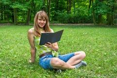 Mujer con la tableta que se sienta en hierba en parque Fotos de archivo libres de regalías