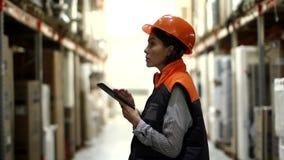 Mujer con la tableta que trabaja en almacenamiento almacen de metraje de vídeo