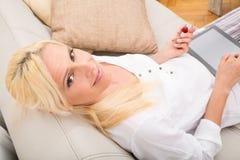Mujer con la tableta y la cereza en el sofá Fotografía de archivo