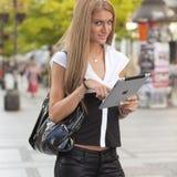 Mujer con la tablilla del iPad en la calle Fotografía de archivo