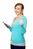 Mujer con la tablilla y los pulgares digitales para arriba Fotos de archivo