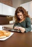 Mujer con la tarjeta de crédito de repaso de la tableta electrónica Fotografía de archivo