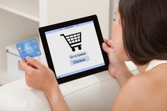 Mujer con la tarjeta de crédito que hace compras en línea en la tableta de Digitaces fotos de archivo