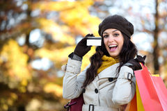 Mujer con la tarjeta de crédito y panieres en otoño Foto de archivo