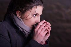Mujer con la taza de bebida caliente durante día frío Fotografía de archivo libre de regalías
