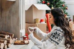 Mujer con la taza de bebida caliente en la Navidad imagen de archivo