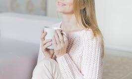 Mujer con la taza de café en manos Fotografía de archivo libre de regalías