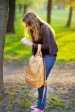 Mujer con la taza de café y de bolso en parque Fotos de archivo libres de regalías
