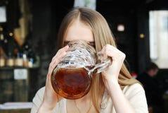 Mujer con la taza de cerveza del alcohol en el café Fotos de archivo