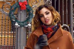 Mujer con la taza de paseo del café en Año Nuevo de la Navidad de la calle de la nieve Foto de archivo