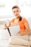 Mujer con la taza de revista de la lectura del café en casa Imagenes de archivo