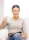 Mujer con la taza de revista de la lectura del café en casa Foto de archivo