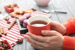Mujer con la taza de té delicioso en la tabla imagen de archivo libre de regalías